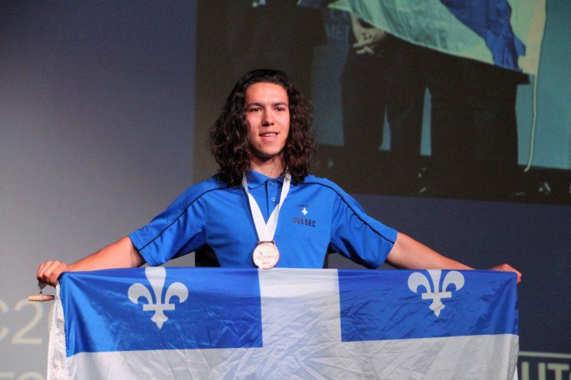 Mathieu Bernier tient fièrement le drapeau du Québec, médaille au cou. | Photo: Gracieuseté