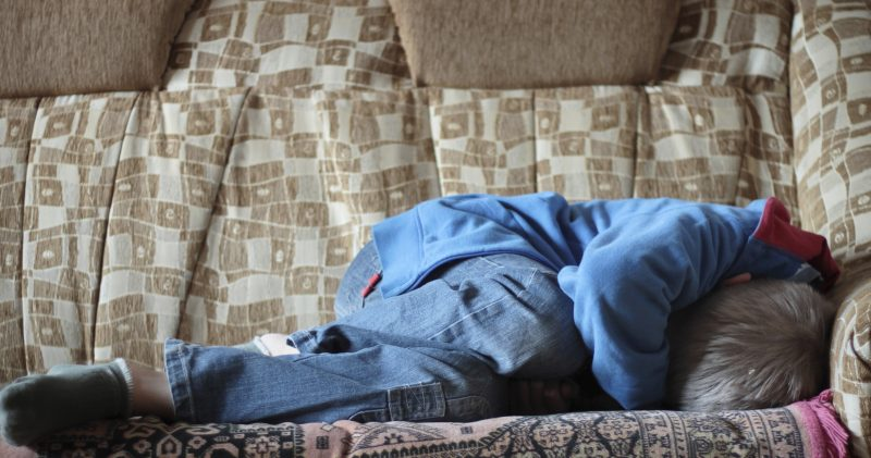 Frightened boy in jeans curled up on bed | Komarovskyy Mykola