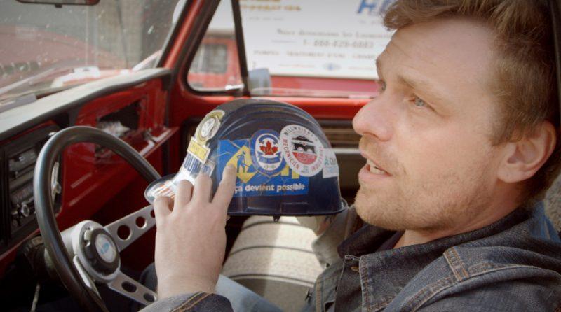 Danic Champoux dans son camion Ford à bord duquel il fait la tournée de ses interlocuteurs. | TC Média = Gracieuseté URBANIA