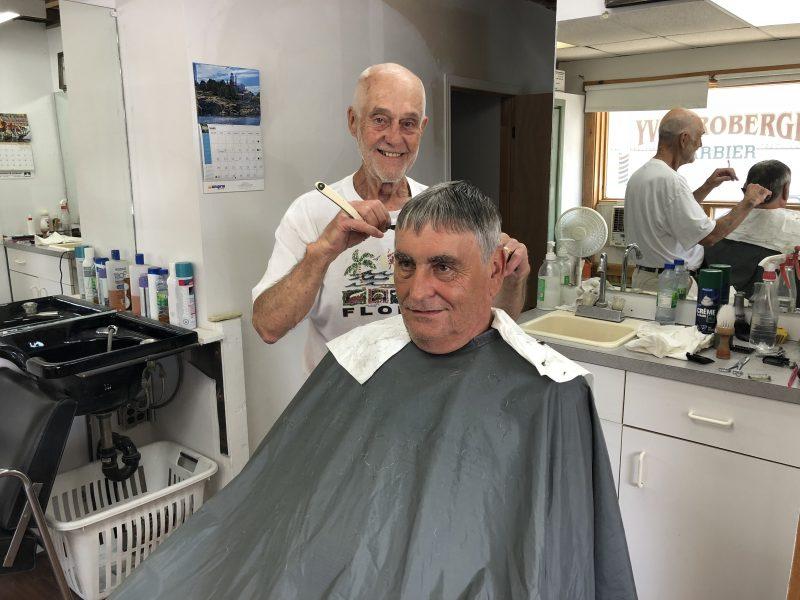 Le barbier Yves Roberge termine la coupe de cheveux de Denis Cloutier, à son salon de la rue du Roi. (Photo: Xavier Demers)