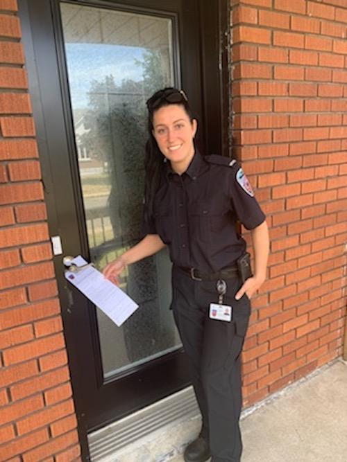 La préventionniste Myriam Laplante appose un accroche-porte informatif pour sensibiliser les citoyens à l'importance d'avoir un avertisseur de fumée fonctionnel.  Photo gracieuseté