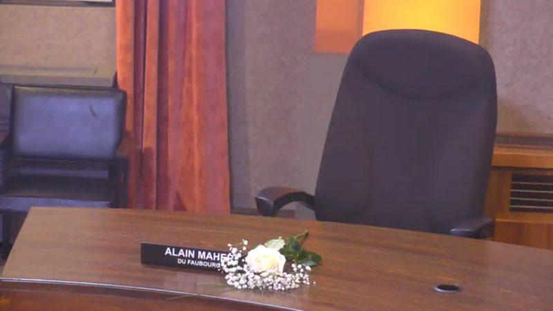 Une gerbe de fleurs a été déposée devant la place du conseiller Alain Maher.  Photo YouTube – Ville de Sorel-Tracy