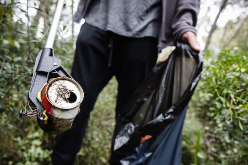 closeup of a caucasian man collecting garbage with a trash grabber stick, in a forest, as an action to clean the natural environment