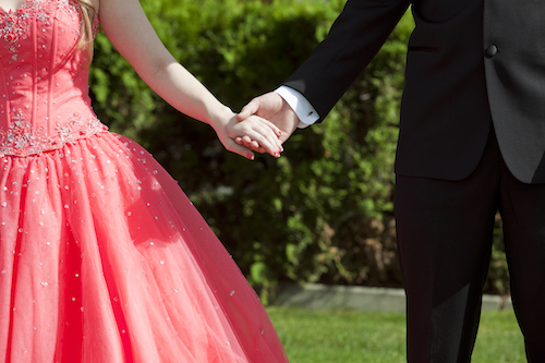 Close cropped outdoor photo of couple dressed in formalwear holding hands