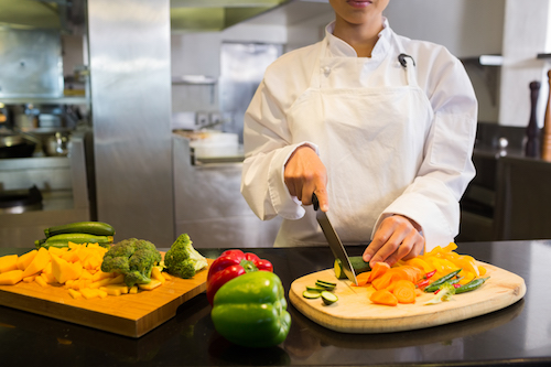 Mid section of a female chef cutting vegetables in the kitchen